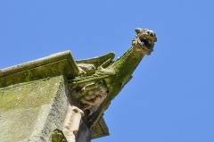 Eglise Saint-Rémy - English:   A laughing, devil-like figure hiding under a gargoyle.  The church of Saint Remy in Dieppe, France.