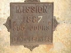 Croix en pierre située sur la place publique - Français:   Inscription sur le socle de la croix de mission