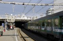 Gare -  Grand trafic ferroviaire de fin d'année. Les locomotives des TGV,  TER, TEOZ  tractent des rames immenses, et se succèdent à de courtes cadences. En 1969, la gare de Montpellier n'était qu'une station sur une grande ligne. Il n'y avait aucune surface couverte, seuls des abris permettaient aux usagers de se protéger plus ou moins de la pluie, ou du soleil, mais jamais du vent. Au fond, on voit se profiler la flèche de la grande verrière encore en construction. Montpellier Saint Roch ressemblera à une véritable gare de TGV.