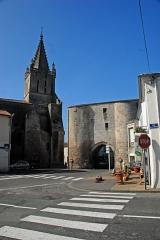 Eglise Saint-Pierre - Deutsch: Pont-l'Abbé-d'Arnoult (17), Kirche, Église de Saint-Pierre de Pont-l'Abbé-d'Arnoult, und ein Stadttor von N-O. Das ehemalige, heute noch wehrhaft wirkend Stadttor besteht aus zwei massiven Rundtürmen ohne außenseitige Fenster Das dazwischen befindliche große Portal wird mit einem angespitzten Rundbogen überspannt. Darüber liegt ein Verbindungstrakt.