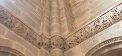 Abbaye - Français:   Frise sculptée romane à droite de la nef, église abbatiale de Hesse, Moselle, France. Coin de la frise avec au centre un visage encadré de deux oiseaux monstrueux.