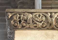 Abbaye - Français:   Frise sculptée romane à droite de la nef, église abbatiale de Hesse, Moselle, France. Détail de deux hommes se tenant la barbe.