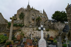 Cimetière communal et son enceinte entourant l'église -  Le Mont-Saint-Michel (Saint Michael's Mount) is an island commune in Normandy, France. It is located about one kilometre (0.6 miles) off the country's northwestern coast and is 100 hectares (247 acres) in size. As of 2009, the island has a population of 44. The island has held strategic fortifications since ancient times and since the 8th century AD has been the seat of the monastery from which it draws its name. The structural composition of the town exemplifies the feudal society that constructed it: on top, God, the abbey and monastery; below, the great halls; then stores and housing; and at the bottom, outside the walls, houses for fishermen and farmers. The commune's position — on an island just 600 metres from land — made it accessible at low tide to the many pilgrims to its abbey, but defensible as an incoming tide stranded, drove off, or drowned would-be assailants. The Mont remained unconquered during the Hundred Years' War; a small garrison fended off a full attack by the English in 1433. The reverse benefits of its natural defence were not lost on Louis XI, who turned the Mont into a prison. Thereafter the abbey began to be used more regularly as a jail during the Ancien Régime. One of France's most recognizable landmarks, visited by more than 3 million people each year, Mont Saint-Michel and its bay are on the UNESCO list of World Heritage Sites. Over 60 buildings within the commune are protected in France as monuments historiques [Wikipedia.org]