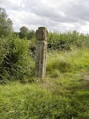 Croix - Français:   Le piétement de la croix est formé de quatre colonnes surmontées de chapiteaux.