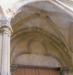 Eglise Saint-Pierre - Il s'agit du portail sud du XIII e siècle de l'église Saint-Pierre de Saint-Julien-du-Sault.  On peut voir le joint des deux claveaux remplacés par la clé de voute gothique ainsi que l'inscription révolutionnaire société populaire.   L'inscription du portail nord ainsi que l'inscription