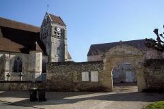 Eglise - Français:   La façade sud de l\'église (vue partielle), et le portail inscrit M.H. de l\'ancien presbytère, actuelle mairie.