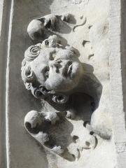 Eglise et le cimetière y attenant -  Tête de chérubin sur l'archivolte de la porte de gauche.
