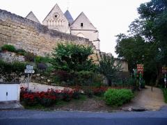 Eglise -  Coucy-le-Château (Aisne, France) - Au pied de la porte de Soissons donnant accès (avec 2 autres) à la cité fortifiée.  Un oriflamme orne chaque côté du sentier longeant le rempart, face à la
