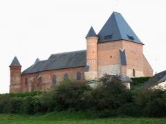 Eglise de Beaurain -  Flavigny-le-Grand-et-Beaurain (Aisne, France) -   L'église fortifiée de Beaurain (façade nord), vue du contrebas de la petite vallée.   Vu sous cet angle au soleil couchant, le clocher ressemble curieusement, avec ses ardoises, à un visage (paupières baissées et nez).