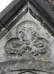 Cimetière de la Madeleine -  Amiens (Somme, France) -  Au cimetière de La Madeleine, une chapelle funéraire néo-gothique.   On remarque au fronton, hormis la dégradation de l'édifice (à gauche, une pierre est tombée), un trilobe décoré d'un motif floral pouvant faire penser à un visage humain).