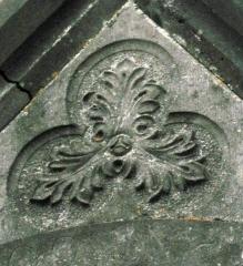 Cimetière de la Madeleine -   Amiens (Somme, France) -  Au cimetière de La Madeleine, une chapelle funéraire néo-gothique.   On remarque au fronton un trilobe décoré d\'un motif floral pouvant faire penser à un visage humain).
