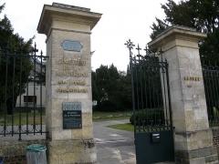 Cimetière de la Madeleine -   Amiens (Somme, France) -  L\'entrée du cimetière de La Madeleine.   Quelques mètres après la grille d\'entrée, plusieurs sentiers sinueux, convergeant vers le pavillon du crématorium, mènent entre les arbres vers une multitude de tombes installées sur les premières pentes de la rive Nord de la Somme.