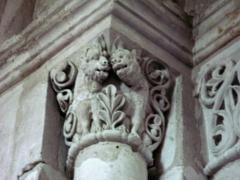 Eglise -  Lucheux (Somme, France) -  Détail de l'intérieur de l'église: chapiteau roman.  Ce chapiteau (numéroté 12 dans le fascicule de 24 pages diffusé par l'Office de tourisme du Doullennais, Lucheux - Merveilles romanes - Les Chapiteaux de l'église Saint-Léger) représente 2 animaux imaginaires et des motifs végétaux. Ils sont presque symétriques.  On remarque aussi que l'astragale (petite moulure en forme de boudin entre le chapiteau et la colonne) est une alternance de billes et de petits cylindres.   Les 2 animaux ont la tête pratiquement l'une contre l'autre, au-dessus d'une large feuille dressée verticalement entre eux et constituée de 5 lobes dont la nervure est profondément creusée. Tous deux ont la bouche entrouverte, celui de droite tire la langue et celui de gauche a les yeux mi-clos. Leur visage, manifestement humain, présente la particularité d'un nez large et écrasé, avec des narines fortement marquées. De part et d'autre, se dresse une volute végétale de 3 boucles, là encore pas parfaitement symétriques.  Il est très vraisemblable que le chapiteau représente une allégorie d'un des 7 péchés capitaux, la luxure. En effet, les 2 animaux n'ont pas de crocs (comme indiqué dans le petit descriptif page 17 de la brochure de l'Office de tourisme). Ces animaux de la forêt sont des singes. Et le singe est habituellement le symbole de la luxure dans l'iconographie chrétienne. La langue tirée et les yeux mi-clos sont un indice non négligeable de la lascivité. Par ailleurs, la forme même de la feuille les séparant (au niveau des pattes et du poitrail) peut évoquer une silhouette humaine accroupie dont les mains se joignent au niveau du sexe.  (Cette photo, prise sans pied, est hélas floue et devra donc être refaite!)