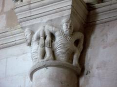 Eglise -  Lucheux (Somme, France) -  Détail de l'intérieur de l'église: chapiteau roman.  Ce chapiteau (numéroté 10 dans le fascicule de 24 pages diffusé par l'Office de tourisme du Doullennais, Lucheux - Merveilles romanes - Les Chapiteaux de l'église Saint-Léger) représente 2 hommes barbus accroupis.  On remarque aussi que l'astragale (petite moulure en forme de boudin entre le chapiteau et la colonne) est simple, anguleuse et sans motif décoratif.  (Ce chapiteau est présenté par une photo dans la brochure de l'Office de tourisme, page 15.)  .  .  (Cette photo, prise sans pied, est hélas floue et devra donc être refaite!)