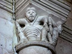 Eglise -  Lucheux (Somme, France) -  Détail de l'intérieur de l'église: chapiteau roman.  Ce chapiteau (numéroté 10 dans le fascicule de 24 pages diffusé par l'Office de tourisme du Doullennais, Lucheux - Merveilles romanes - Les Chapiteaux de l'église Saint-Léger) représente 2 hommes barbus accroupis.  On remarque aussi que l'astragale (petite moulure en forme de boudin entre le chapiteau et la colonne) est simple, anguleuse et sans motif décoratif.  (Ce chapiteau est présenté par une photo dans la brochure de l'Office de tourisme, page 15.)  .   .