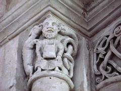 Eglise -  Lucheux (Somme, France) -  Détail de l'intérieur de l'église: chapiteau roman.  Ce chapiteau (numéroté 11 dans le fascicule de 24 pages diffusé par l'Office de tourisme du Doullennais, Lucheux - Merveilles romanes - Les Chapiteaux de l'église Saint-Léger) représente 2 animaux murmurant aux oreilles d'un homme.  On remarque aussi que l'astragale (petite moulure en forme de boudin entre le chapiteau et la colonne) est très simple et sans motifs décoratifs.   .  Il est très vraisemblable que le chapiteau représente une allégorie d'un des 7 péchés capitaux, l'envie. En effet, l'animal de gauche est un chien et celui de droite est un serpent, figures symboliques traditionnelles de l'envie dans l'iconographie chrétienne.  Il faut pourtant noter que l'homme au centre porte sur la poitrine et le ventre une sacoche carrée, suspendue à son cou par une lanière. Or, la présence d'une bourse ou d'un sac sur des chapitaux d'autres églises romanes fait référence à un autre péché capital, l'avarice.   Doit-on penser alors que ce chapiteau a été conçu pour représenter 2 péchés en même temps?