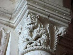 Eglise -  Lucheux (Somme, France) -  Détail de l'intérieur de l'église: chapiteau roman.  Ce chapiteau (numéroté 1 dans le fascicule de 24 pages diffusé par l'Office de tourisme du Doullennais, Lucheux - Merveilles romanes - Les Chapiteaux de l'église Saint-Léger) représente un monstre et une tête d'homme.  On remarque aussi que l'astragale (petite moulure en forme de boudin entre le chapiteau et la colonne) a un motif décoratif simple, une torsade.   .  Il est très vraisemblable que le chapiteau représente une allégorie d'un des 7 péchés capitaux, la grourmandise. En effet, l'animal monstrueux est un ours, figure symbolique traditionnelle de la gloutonnerie dans l'iconographie chrétienne.  L'animal a un pelage manifestement très épais, il tire la langue exagérément, et son corps est particulièrement gros, voire obèse. Il est équipé de cornes - un des attributs du diable - qui se rejoignent au-dessus de sa tête. Ses pattes avant reposent sur une fleur de lys. Une autre fleur de lys est représentée en haut à gauche.   A sa droite, une large palme se dresse, au-delà de laquelle surgit l'élégant visage d'un homme jeune et barbu (le Christ?).