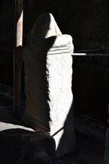 Evêché - Cippe surmonté d'une pomme de pin avec inscription d'époque romaine, découvert à Anglefort en 1879-1980, lors du creusement du canal de dérivation du Rhône, conservé depuis au moins 1987 dans le jardin Jean-Pierre Camus derrière l'évéché à Belley (Ain).   165 x 61 x 42 cm. Inscription: Aux Dieux mânes de Ruffius Severus, fils de Scotus, Rufinula, fille de Rufus, à l'âge de 52 ans, sa petite-fille, héritière, a pris soin de poser cette inscription.