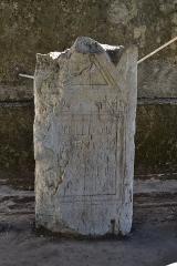Evêché - Stèle à fronton encadrée d'antéfixes avec décor (rosace? croissnt de lune?) avec inscription d'époque romaine, découverte à Anglefort en 1879-1980, lors du creusement du canal de dérivation du Rhône, conservé depuis au moins 1987 dans le jardin Jean-Pierre Camus derrière l'évéché à Belley (Ain).   156 x 76 x 33 cm. Références: AE 1988, 0879 = Carte archéologique de la Gaule CAG 01 p. 139 = Epigraphische Datenbank Heidelberg [1] = Le Bugey 1987 p. 356-357 Raymond Chevallier Monument 5)