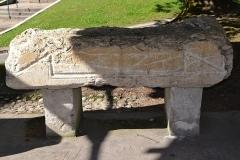 Evêché - Partie inférieure d'un sarcophage d'enfant avec inscription d'époque romaine, découvert à Anglefort en 1879-1980, lors du creusement du canal de dérivation du Rhône, conservé depuis au moins 1987 dans le jardin Jean-Pierre Camus derrière l'évéché à Belley (Ain).   194 x 45 x 60 cm.  Inscription: curaverunt ponen/dum sub ascia dedicatum / p(onendum) c(uravit) m(ater) et au(ia) d(edicavit) Références:  AE 1988, 0878 = Carte archéologique de la Gaule CAG 01 p. 139 = Epigraphische Datenbank Heidelberg HD009158 = Le Bugey 1987 p. 356-357 Raymond Chevallier Monument 5)