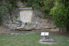 """Bas-relief mithriaque -  1.30 meters long and 1.15 meters high, it is the only bas-relief directly sculpted in the rock that can be seen in France. In the 3rd century, this bas-relief was indeed the back of a temple, Mithraeum, which went all the way to the riverside. The bas-relief was to be demolished in 1880, when the railroad was built, but Priest Paradis was strongly opposed to this decision. He managed to have it preserved and protected. The worship of Mithra is of Indo-Iranian origins and was brought here by the Romans for their fight against Gallic gods and beliefs, druids and Christians. On the bas-relief, the god is represented by a young man riding the bull he is sacrificing. The ears of wheat gushing out of under its tail symbolize the new life brought by the animal's death. In front, one can see a cartouche with Latin inscriptions. Among the several translations which were made to French, the most commonly accepted is: """"A la divinité de Mithra, au Soleil très grand, Titus Furius Sabinus a fait faire et dédier cette image du dieu invincible à ses frais"""".  The worship of Mithra reached a peak in the 3rd and 4th centuries, a time when it transformed into a worship of the sun and became a rival of Christianity. As every pagan religion, the worship of Mithra was declared illegal in 391. Mithra was born in a cave near a water source, thus some rites took place into such caves. It was an initiatory religion for which men had to prove their strength. There were 7 ranks. This worship was strongly connected to astronomy."""