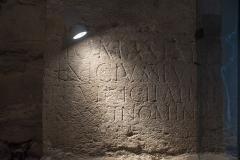 Eglise - Français:   Pierre romaine située à la base du mur intérieur ouest portant une dédicace à Jupiter par Vinicius Servirus.