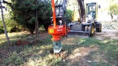 Château de Bourgon - English: A hydraulic rotor stump remover work with a excavator for recover a tree roots.