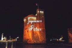 Slip way - Illumination en orange des tours du port de La Rochelle pour les fêtes de fin d'année 2015. Les inscriptions lumineuses «Joyeuses Fêtes» sur les tours sont créées avec des projecteurs situés sur le Quai des Sardiniers. La Rochelle, Charente-Maritime, France.