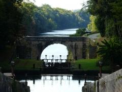 Canal de Lalinde (groupe des écluses, y compris le bassin de croisement, ponts supérieur et inférieur, façades et toitures des maisons éclusières aval et amont, lieudit Tuilières) - Français:   Le groupe d\'écluses de Tuilières sur le canal de Lalinde, Mouleydier, Dordogne, France. Au premier plan, le bassin de croisement. Au second plan, le pont aval, puis la Dordogne. La ligne d\'arbres au-delà de la Dordogne se trouve sur la commune de Saint-Agne.