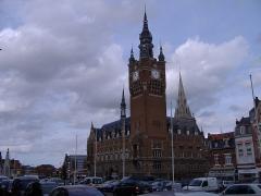 Hôtel de ville -  Vue de la tour du Beffroi de style flamand par la tranche, et du bâtiment attenant. Il est construit en brique d'un rouge foncé comme la majorité des édifices de la région des Flandres, mais aussi des Paus-Bas ou du Nord-Ouest de l'Allemagne (Hildesheim par exemple). Le ciel est gris et nuageux comme souvent ici, où comme le dit Brel les cathédrales sont les uniques montagnes, et celle-ci crève le ciel de son clocher.