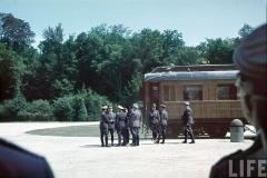 Clairière de l'Armistice - Le 21 juin 1940, devant le wagon de l'Armistice de Rethondes, dans la clairière de l'Armistice de la forêt de Compiègne, Hitler discute avec de hauts dignitaires nazis et ses généraux, avant le lancement des négociations de l'armistice qui sera signé le lendemain (le 22 juin 1940) entre la France vaincue et l'Allemagne victorieuse.  Cette signature va avoir lieu au même endroit que pour l'armistice du 11 novembre 1918 à l'époque où l'Allemagne était vaincue: dans le wagon qui a été sorti de son abri pour l'occasion. Les personnes qui peuvent être reconnues sont, de gauche à droite:  Joachim von Ribbentrop, ministre des Afffaires étrangères du Reich; Adolf Hitler, chancelier du Reich; Hermann Göring de dos, Generalfeldmarschall, commandant en chef de la Luftwaffe; Erich Raeder caché, Großadmiral, commandant en chef de la Kriegsmarine; probablement Walther von Brauchitsch caché, Generaloberst, commandant en chef de l'Armée de terre; probablement Rudolf Hess de dos, suppléant de Hitler à la tête du parti nazi, chef de la chancellerie du parti.