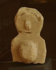 Temple gallo-romain de la forêt d'Halatte -  Ex-voto en pierre provenant du sanctuaire gallo-romain de la forêt d\'Halatte, près de Senlis: femme enceinte? (Un certain nombre d\'ex-votos du site sont liés à une demande de fécondité). Ce sanctuaire, consacré à une divinité guérisseuse non identifiée, a été bâti vers 50 + JC. On y a retrouvé plus de 350 ex-voto; les ex-voto en pierre étaient à l\'origine enduits et peints. Musée de Laon (exposition temporaire du fond du Musée de Senlis).