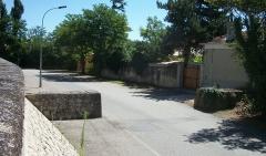 Digue d'enceinte de la ville - Français:   Digue de Caderousse (Vaucluse, France). Muret secondaire perpendiculaire à l\'ouvrage, pour retarder la montée de l\'eau par le point bas sur la route au pied de la digue.