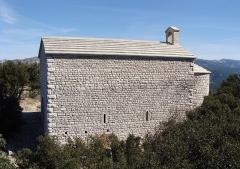 Chapelle Saint-André-de-Julhans - Français:   Le mur latéral sud de chapelle: pierres calcaires taillées rectangulaires, en rangs horizontaux irréguliers, angles renforcés par des pierres plus importantes. Deux petits fenestrons en position basse.