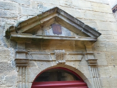Immeuble - Français:   Fronton triangulaire surmontant une porte de l\'immeuble situé 9, rue Montaigne. Cette porte est sur la façade donnant du côté de l\'impasse de La Vieille-Poste (Sarlat-la-Canéda, Dordogne)
