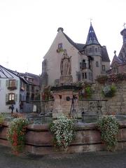 Fontaine datée de 1557 située devant l'Ecole des Filles - Français:   Fontaine de Saint-Léon et château des comtes d\'Eguisheim à Eguisheim (Haut-Rhin, France).