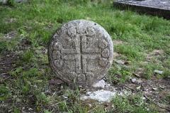 Eglise et ancien cimetière -   Discoid stele decorated with an Occitan cross..