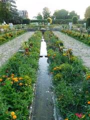 Jardin des Prés Fichaux - Français:   Rigole fleurie (pétunia, œillet d\'Inde, canna, etc.), où des pigeons viennent se désaltérer (un est visible au loin); jardin des Prés-Fichaux, Bourges, Cher, France.