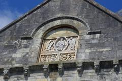Eglise Notre-Dame - Châtillon-sur-Indre (Indre)  Eglise Notre-Dame.  Partie supérieure du transept sud.  Sculpture romane du pignon représentant un Christ bénissant entre deux anges.  Le bandeau inférieur représente:  à gauche un épisode de la vie de saint Outrille*; un pilleur d\'église puni par saint Outrille.  à droite les méchants sont précipités par des diables dans la gueule d\'un léviathan figurant l\'Enfer.  Cette sculpture provient vraissemblablement d\'un édifice antérieur.     Saint-Outrille: Austregisilus, évèque de Bourges au commencement du VIIe siècle. Il semble être le premier archevêque d\'ascendance wisigothe, tous les archevêques antérieurs, étant issus d\'une famille romaine. Il avait passé sa jeunesse à la cour des rois de Bourgogne. Il refusa une épouse pour devenir prêtre à Lyon, puis évêque de Bourges .  Il acquit l\'estime du peuple en chassant un seigneur malfaisant que saint Outrille força lui-même, une épée à la main, à déguerpir et à pratiquer son brigandage ailleurs.  \