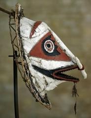Ancien hôtel-Dieu - Issoudun (Indre)  Musée de l\'Hospice Saint-Roch.  Masque du groupe Elema. Papouasie-Nouvelle-Guinée. XIXe siècle.  Le groupe Elema s\'étend le long de la côte est du Golfe de Papouasie, depuis le fleuve Purari au Cap Possession.  Les masques sont fabriqués par les hommes, dans les maisons cérémonielles à l'abri du regard des femmes et des enfants. Ils sont formés d'une structure en rotin et de jonc sur laquelle est fixée une étoffe d'écorce battue, le tapa, structure végétale frappée selon une technique répandue en Océanie. Les yeux ronds, le nez long en relief, l'harmonie des pigments, rouge, blanc et noir comme les motifs triangulaires sont caractéristiques de leur style. Ce sont des masques de danse, portés au rythme du tambour, pour les cérémonies destinées à faire revivre les esprits et à initier les jeunes adultes. Les masques Kovave de forme conique, à la bouche ouverte et menaçante, sont voués à éveiller les esprits de la brousse. A l'issue des cérémonies les masques étaient ordinairement brûlés d'où leur rareté parmi les collections ethnographiques internationales.  webmuseo.com/ws/musee-issoudun/app/collection/record/6