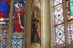 Ancienne collégiale Sainte-Menehould, actuelle église Saint-Sulpice - Palluau-sur-Indre (Indre)  Église Saint-Sulpice, anciennement collégiale Sainte Menehould.  Statue en pierre polychrome de sainte Menehould datant du XVe siècle.  Sainte Menehould naît à Perthes en Champagne au début du Ve siècle. Elle est la cadette des sept filles du gouverneur du Perthois, le comte Sigmarus. Elles sont élevées pieusement par le prêtre Eugène. Toutes prirent le voile et l\'évêque de Châlons, saint Alpin, recevra leurs vœux. Sainte Menehould prend la direction d\'un hospice et serait à l\'origine de plusieurs guérisons miraculeuses. Elle meurt  le 14 octobre, jour de sa fête, 490 ou 499.