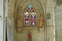 Ancienne collégiale Sainte-Menehould, actuelle église Saint-Sulpice - Palluau-sur-Indre (Indre).    Ancienne collégiale Sainte-Menehould, actuelle église Saint-Sulpice (XIIe, XIVe, XVe, début XVIe). Chapelle nord-est.  Verrière représentant saint Roch et saint Sulpice et au tympan la Crucifixion. Cette verrière est partiellement du XVIe siècle, complétée au XIXe siècle.  Statues: A gauche, sainte Marie-Madeleine, à droite, le Christ ressuscité apparaissant en jardinier à Marie-Madeleine.  L\'ancienne collégiale est devenue église Saint-Sulpice après le Concordat en 1801. Les stalles sont du XVe siècle, les statues polychromes du Moyen-Âge et de l\'époque moderne.     <a href=\