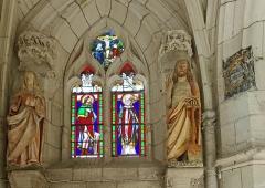Ancienne collégiale Sainte-Menehould, actuelle église Saint-Sulpice - Palluau-sur-Indre (Indre).    Ancienne collégiale Sainte-Menehould, actuelle église Saint-Sulpice (XIIe, XIVe, XVe, début XVIe). Chapelle nord-est.  Verrière représentant saint Roch et saint Sulpice et au tympan la Crucifixion. Cette verrière est partiellement du XVIe siècle, complétée au XIXe siècle.    L\'ancienne collégiale est devenue église Saint-Sulpice après le Concordat en 1801. Les stalles sont du XVe siècle, les statues polychromes du Moyen-Âge et de l\'époque moderne.     <a href=\