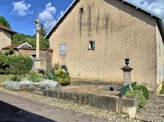 Croix en pierre située sur la place publique - Français:   La fontaine et la croix