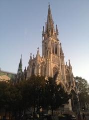 Basilique Saint-Epvre - Vue de la face principale de la basilique et de l'un de ses côtés; photo prise légèrement de biais. L'entrée est en grande partie masquée par les arbres, en bas, mais l'on peut bien admirer le clocher et l'horloge, illuminés par les dernières lueurs du jour.