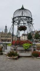 Puits - Français:   Le vieux puits (pierre et fer forgé), situé à l\'origine sur la place de l\'Hôtel de Ville, déplacé place du Marché puis dans un square près de la basilique (square Winston-Churchill cité plus haut). En septembre 2008, il a été décidé de réinstaller le vieux puits place de l\'Hôtel de Ville. Fin mai 2009, après avoir été restauré, il a retrouvé son lieu d\'implantation d\'origine.