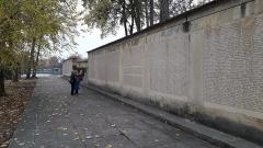 Parc de la Tête-d'Or - Cénotaphe avec le nom des morts pour la France,  monument aux morts de l'Île aux cygnes du parc de la Tête d'or, deux personnages âgées venues photographier les noms de leurs aïeuls