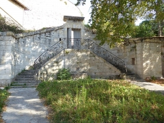 Ancienne tannerie royale - English: Royal Tannery of Lectoure - double semi-circular staircase and railing of pedestrian entrance in triangular courtyard showing ravelin behind