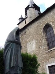 Monument aux morts - Français:   Campan - Église Saint-Jean-Baptiste et la femme au capulet