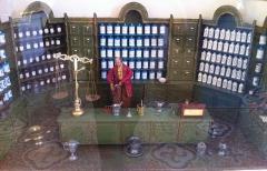 Hôtel-Dieu - Français:   Maquette d\'une apothicairerie a 19e siècle.  L\'apothicaire se tient derrière sa longue table qui sert à la fois de plan de travail et de comptoir de vente. Sur les étagères sont rangés de nombreux pots en faïences. Des tiroirs en bois, et non des boites, servent à conserver les plantes. Sur le comptoir se trouvent les instruments: balance, motiers, entonnoir, cruches ...  Maquette (bois, métal ...) réalisée par un collectionneur, 1ere moitié du 20e siècle.